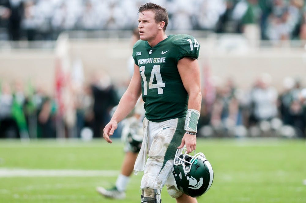 Junior quarterback Brian Lewerke (14) walks off the field after the game against Northwestern at Spartan Stadium on Oct. 6, 2018. The Spartans trail the Wildcats at halftime 14-6.