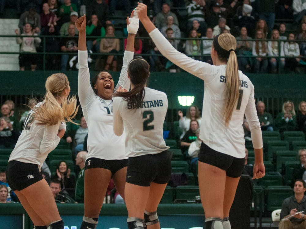<p>The Spartans volleyball team celebrate after a scored point during the game against Wisconsin on Nov. 9, 2014, at Jenison Field House. The Badgers defeated the Spartans, 3-0.  Aerika Williams/The State News </p>