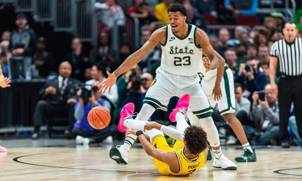 Sophomore forward Xavier Tillman forces Michigan's Jordan Poole into turning the ball over during the Big 10 Tournament Championship. The Spartans beat the Wolverines, 65-60, at the United Center on March 17, 2019.