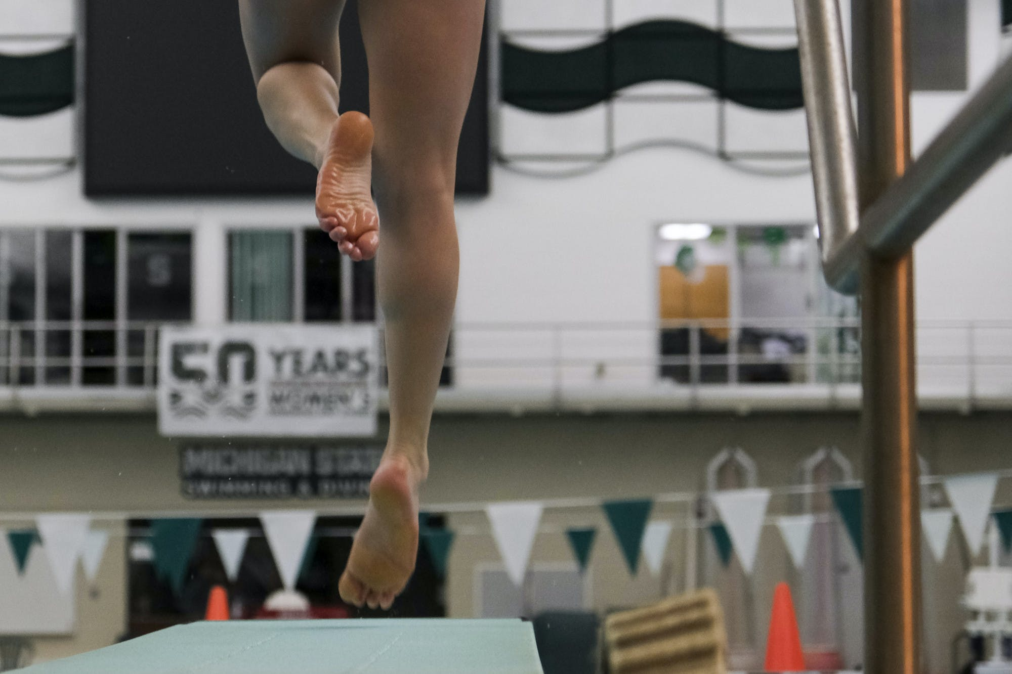 A person jumps up from a diving board with one leg straight and one leg bent. In the background are green and white pennants hanging on a string.