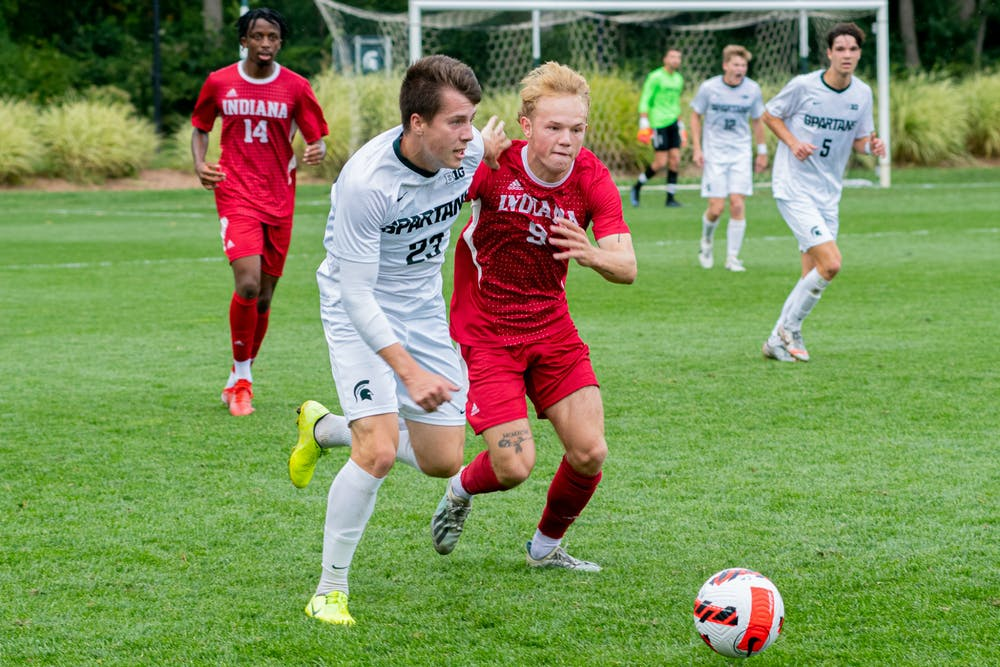 <p>Senior midfielder Luis Sala (23) intertwines arms with Indiana freshman forward Samuel Sarver (9), as they make a play on the ball. The Spartans faced off against the Hoosiers at DeMartin Field on Sept. 26, 2021.</p>