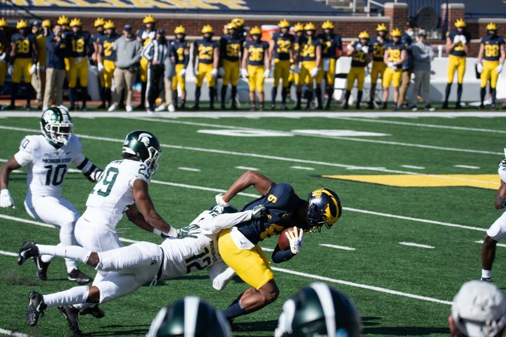 MSU cornerback, Chris Johnson (12),  tackles U of M wide reciever, Cornelius Johnson (6).