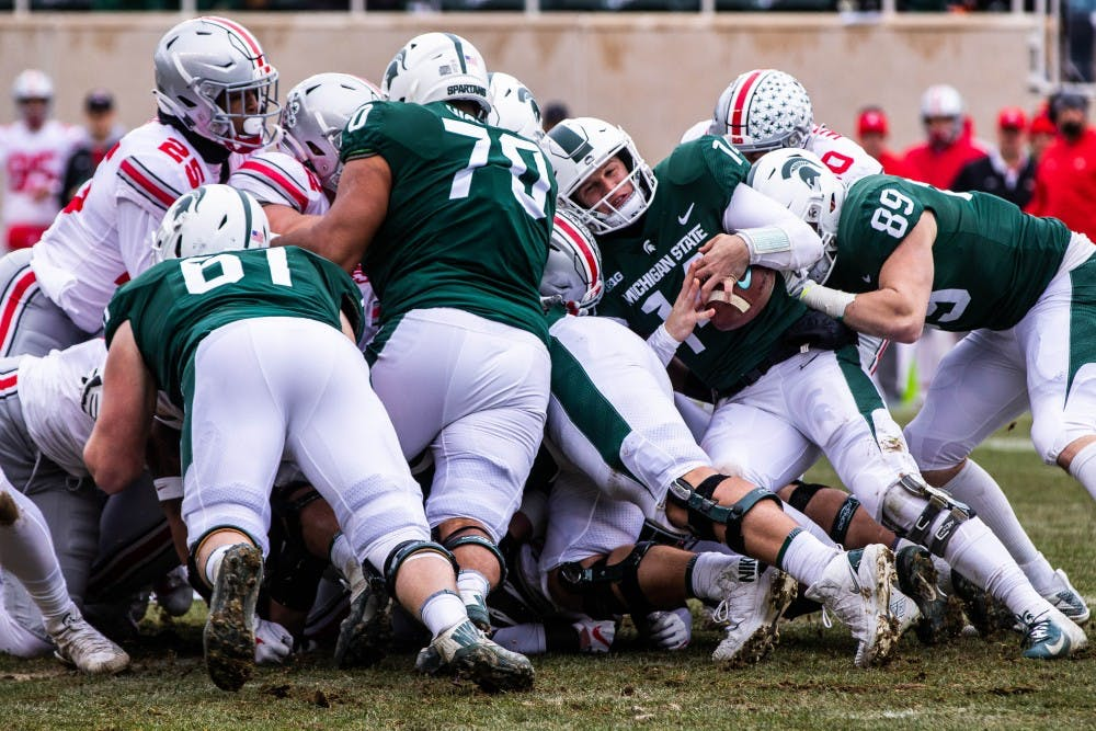 Junior quarterback Brian Lewerke (14) pushes for a first down during the game against Ohio State Nov. 10, 2018.
