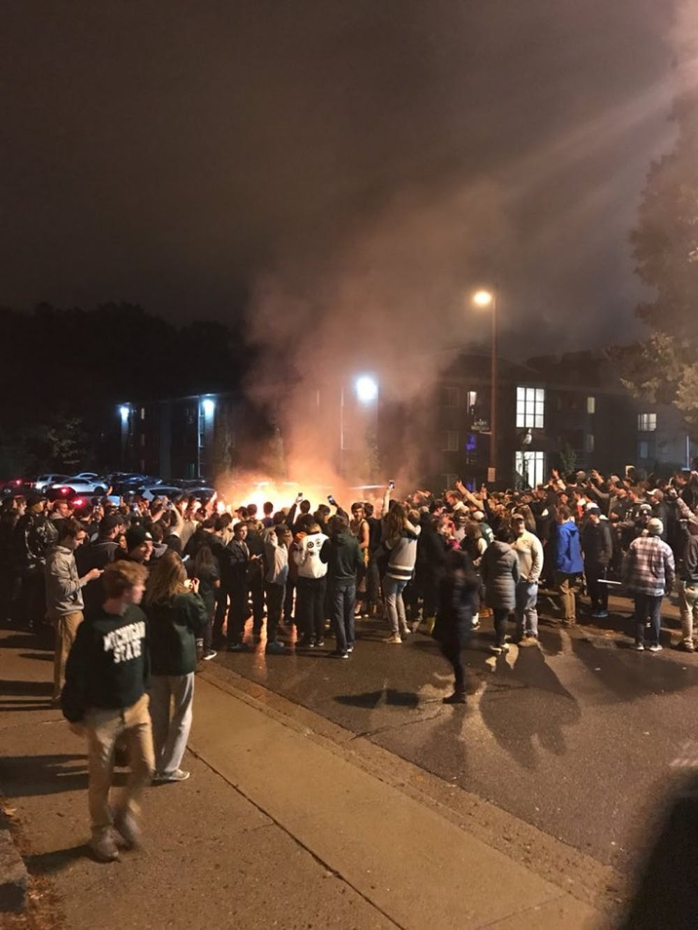 Dozens gather around furniture set on fire to celebrate MSU's win over Penn State. Officials extinguished the fire by approximately 7:40 p.m.