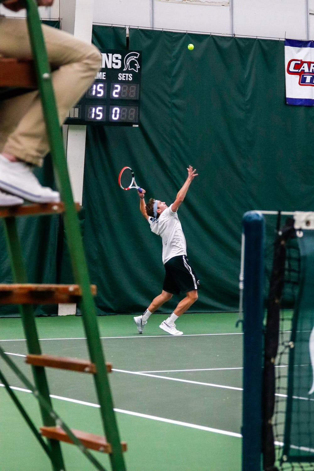 <p>Freshman Drew Keene serves during a doubles match against Niagara at the MSU Tennis Center Jan. 25, 2020. The Spartans defeated the Purple Eagles, 7-0.</p>