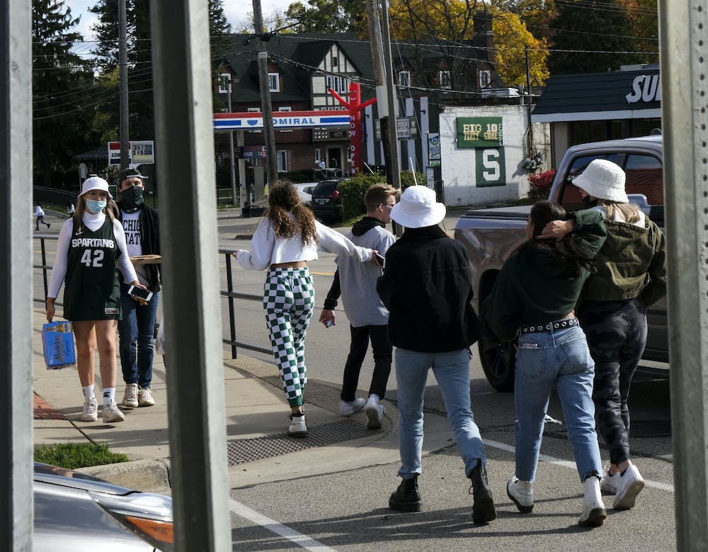 Green and white adorning MSU football fans roaming the streets during MSU's first football game among Coronavirus conditions on October 24, 2020.