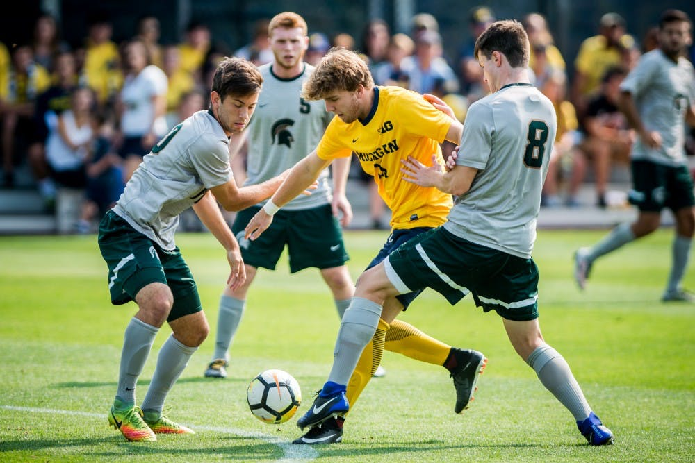 Sophomore midfielder Giuseppe Barone (10) and senior defender Brad Centala (8) attempt to take the ball from Michigan forward Jack Hallahan (11) during the game against the University of Michigan on Sept. 17, 2017 at U-M Soccer Stadium. The Spartans defeated the Wolverines, 1-0.