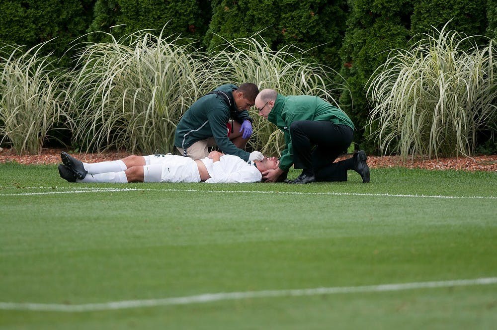 <p>Senior forward Adam Montague receives help after getting injured during the game against Valparaiso on Sept. 11, 2014, at DeMartin Stadium at Old College Field. The Crusaders defeated the Spartans 1-0 in regulation time.  Aerika Williams/The State News</p>