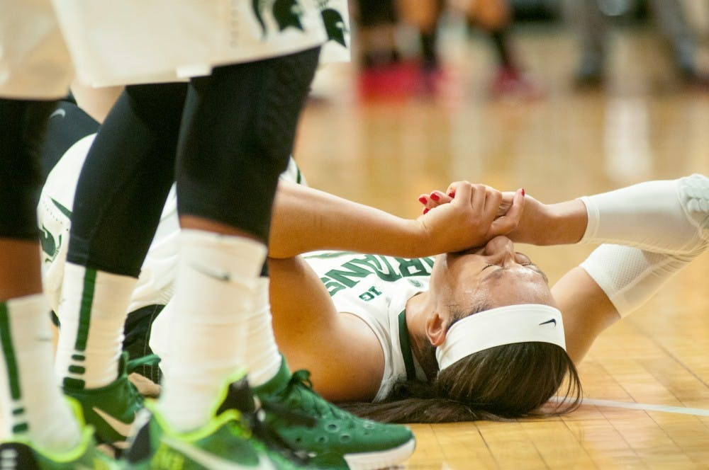 Junior forward Aerial Powers closes her eyes in agony on Dec, 3, 2015 during the second half of the game against Louisville at Breslin Center. Powers was going for a layup when she landed on her left leg badly. The Spartans were defeated by the Cardinals, 78-85.
