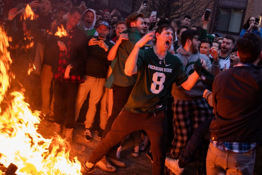 A fan screams as a couch burns  after MSU's victory over Duke in the Elite Eight in Cedar Village Apartments March 31, 2019.