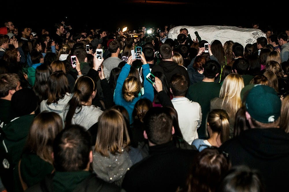 <p>Students stand and listen to men's basketball head coach Tom Izzo at the Rock on Farm Lane on April 9, 2014, in remembrance of Lacey Holsworth at her memorial. Holsworth was a good friend of senior forward Adreian Payne and passed away April 8 after a battle with cancer. Erin Hampton/The State News</p>