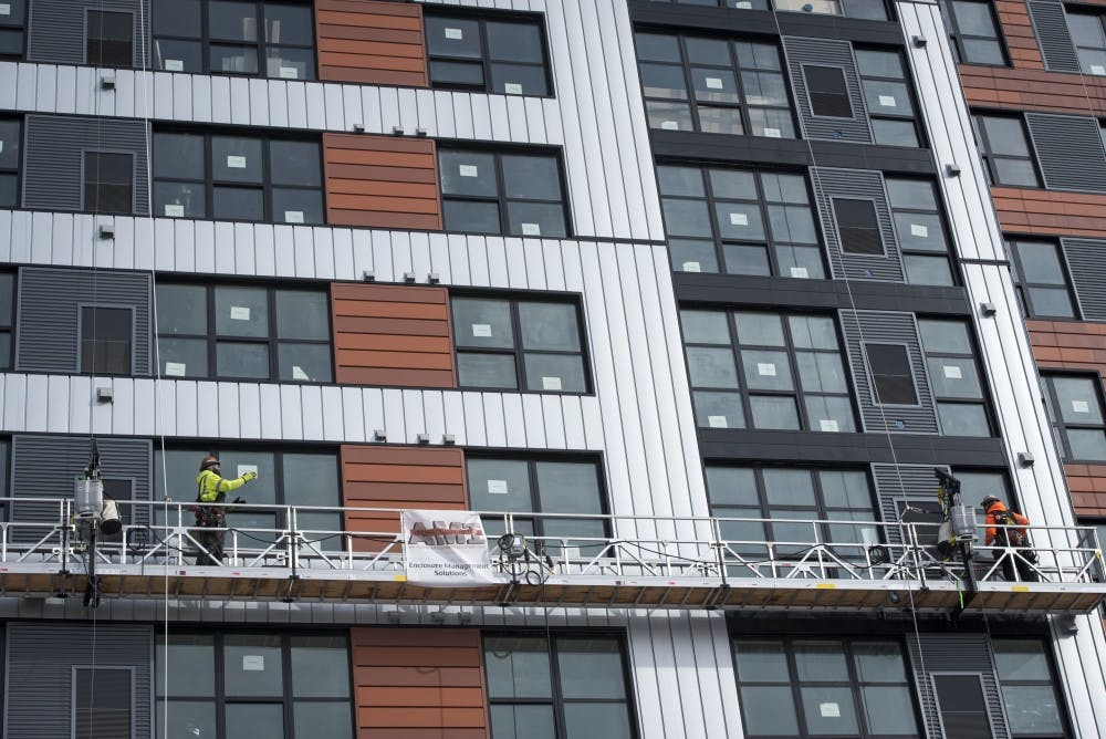 <p>Construction workers work at the Center City Project along Grand River Avenue on Feb. 14, 2019. Nic Antaya/The State News</p>
