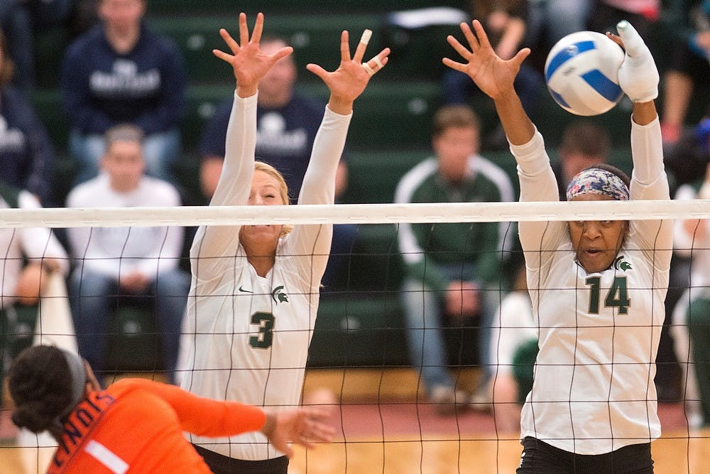 <p>Sophomore middle blocker Autumn Christenson, 3, and senior middle blocker/outside hitter Jazmine White go up to block Illinois outside hitter Morganne Criswell's spike Oct. 31, 2014, at Jenison Field House. The Spartans lost, 3-1. Julia Nagy/The State News</p>