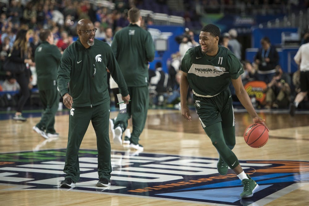 Michigan State assistant coach Mike Garland, left, jokes with freshman forward Aaron Henry (11) during Michigan State's NCAA Men's Basketball Final Four open practice at U.S. Bank Stadium in Minneapolis on April 5, 2019. (Nic Antaya/The State News)