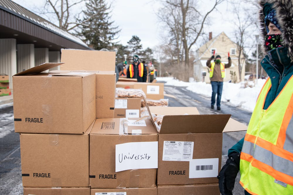 """Katie Hanson, a member of the United Methodist Church-University,  volunteers at a Greater Lansing Food Bank distribution at the University Lutheran Church on Jan. 28, 2021. """"It's a way we can contribute and do so safely."""""""