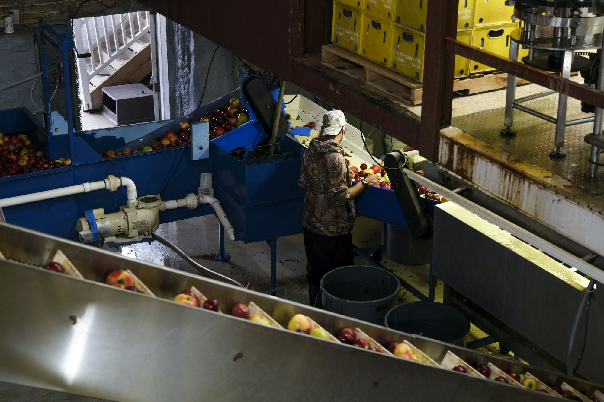 An employee at Uncle John's Cider Mill is surrounded by machinery where cider is made.