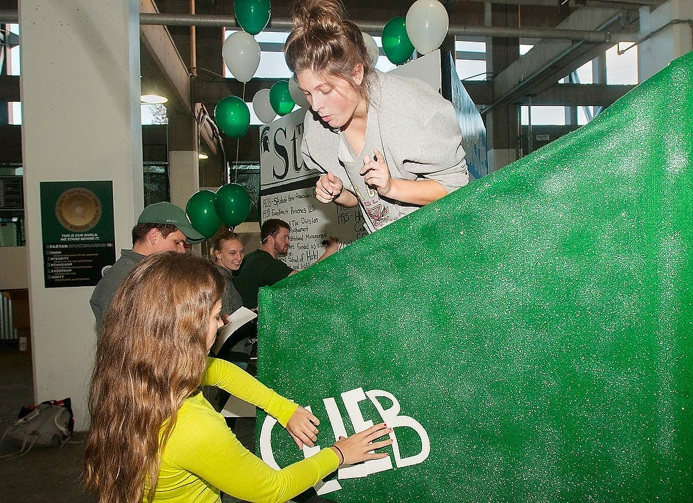 <p>Hospitality business seniors Taylor Pahl, left, and Jessica Dupont work on their float for the School of Hospitality Business on Sept. 24, 2014, at Spartan Stadium. The float will be seen at the MSU Homecoming Parade on Friday. This year's parade float theme is Spartans make headlines.  Raymond Williams/The State News</p>