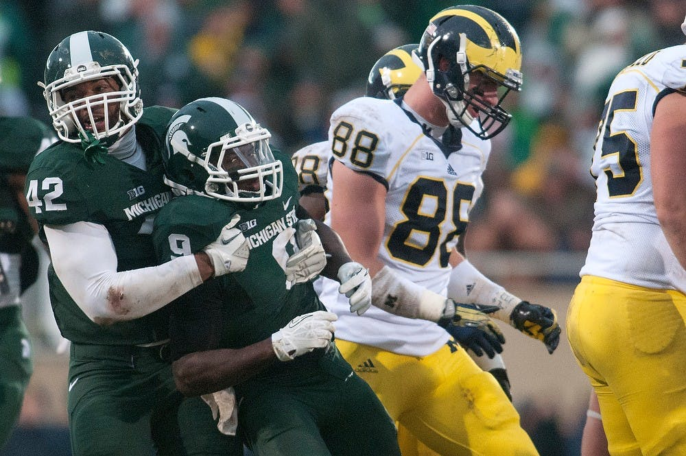 <p>Senior defensive end Denzel Drone pulls senior safety Isaiah Lewis from from a huddle of Wolverines on Nov. 2, 2013, at Spartan Stadium. The Spartans won, 29-6. Julia Nagy/The State News </p>
