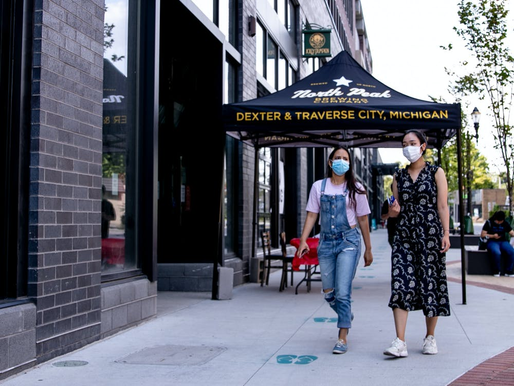 Two people walk in front of Jolly Pumpkin in East Lansing wearing their masks August 24, 2020.