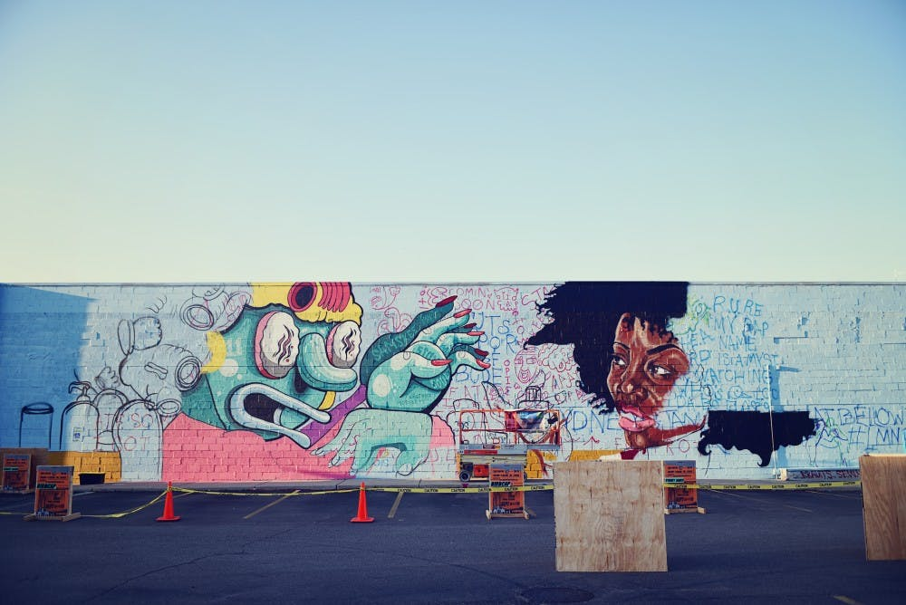 <p>Partially completed mural in Lansing with the Below the Stacks mural art festival. COURTESY OF ALEXIS ROSADO</p>