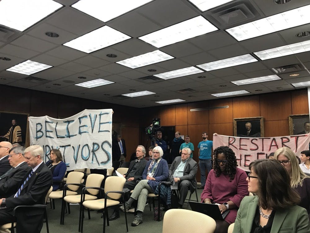 <p>Members of the MSU community hold up signs during the Board of Trustees meeting on Oct. 26, 2018.&nbsp;</p>