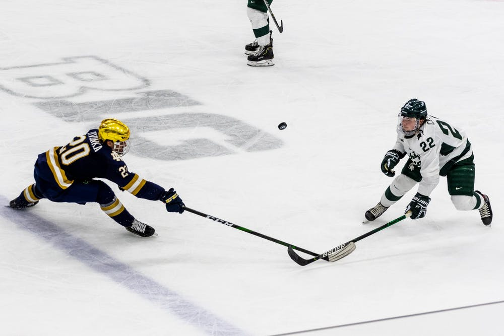 <p>Sophomore defender Dennis Cesana (right) and Notre Dame center Jake Pivonka both attempt to bring down the puck. The Spartans were defeated by the Fighting Irish, 2-1, at Munn Ice Arena on Nov. 22, 2019. </p>