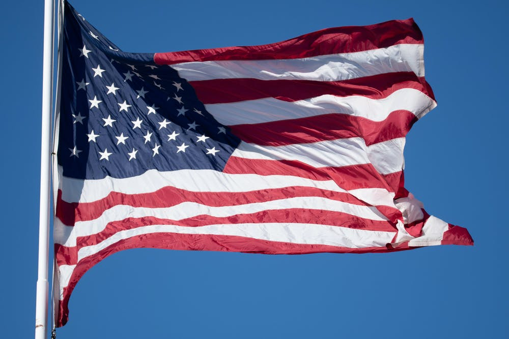 <p>An American flag flies in the wind in The Big House on Oct. 31, 2020.</p>
