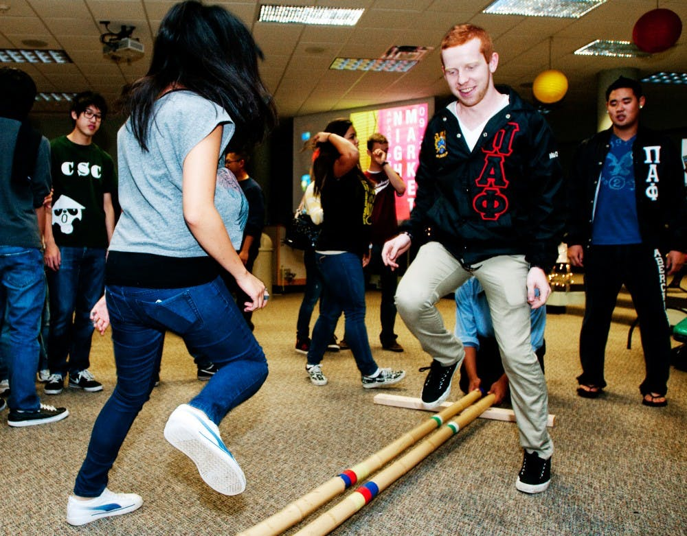 Civil engineering junior Jane Lee and anthropology junior Josh Jennings perform a Filipino dance called Tinikling, which involves hitting two bamboo sticks on the ground in coordination with dancers. The activity was one of several at Night Market that introduced students to different Asian American cultures on Monday night at Wonders Hall Kiva. Josh Radtke/The State News
