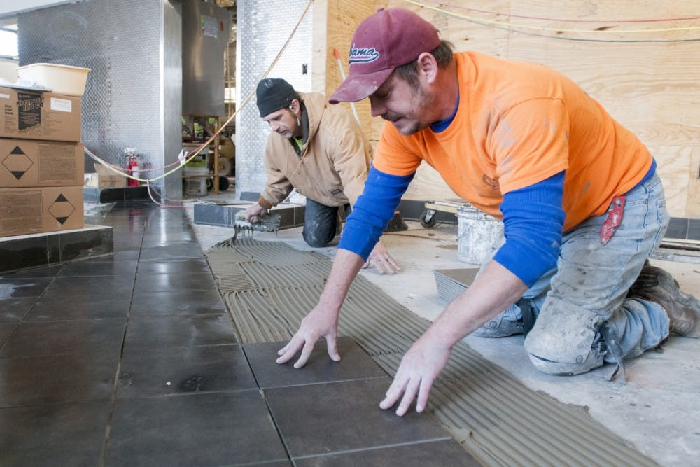 From left, Atlanta Georgia residents Derrick Johnson and Shane Roberts install tiles on Feb. 6, 2017 at the new Chick fil-A in Okemos. The construction is said to be completed by Mar. 30, 2017.