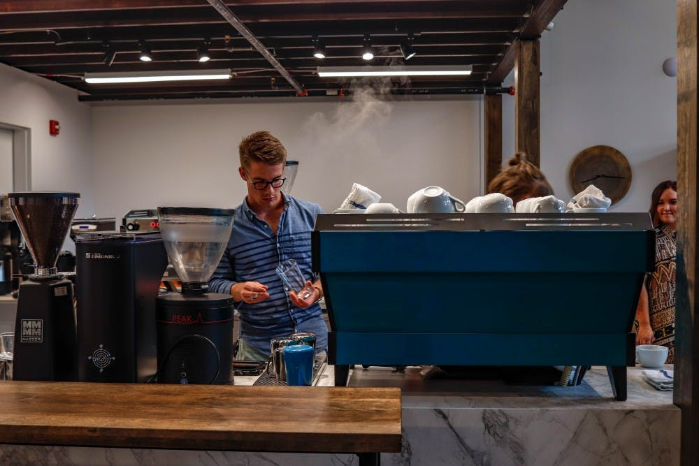 <p>An employee prepares free coffee for those at the press release event at Foster Coffee Co in East Lansing on Sept. 11, 2019.</p>