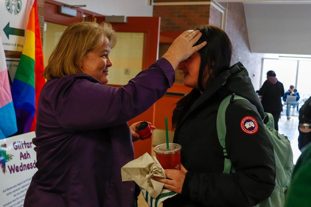 <p>Rev. Donna McNiel marks a student's forehead in Wells Hall at the Glitter Ash Wednesday event put on by Canterbury MSU, All Saints Episcopal Church and Edgewood United Church of Christ on Feb. 26, 2020.</p>