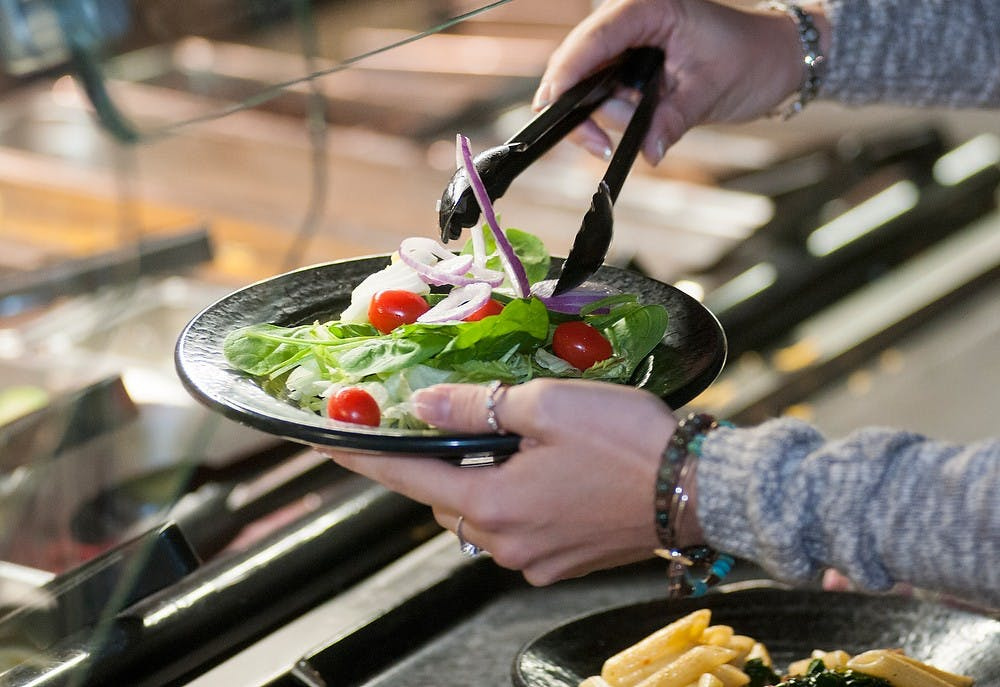 <p>Advertising senior Ashley Noll serves herself a salad on Sept. 11, 2014, at Case Hall's Salad and Sushi Bar. <strong>Raymond Williams/The State News</strong></p>