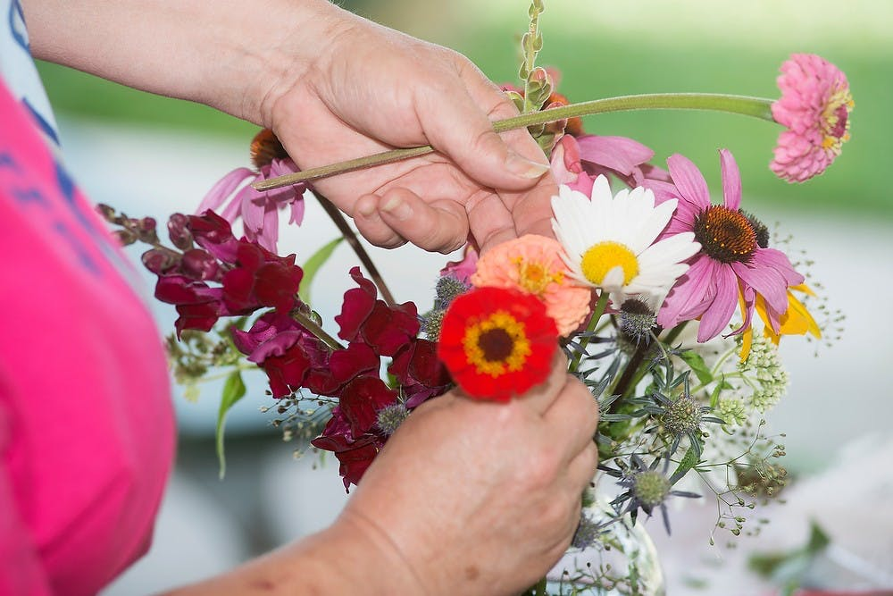 <p>Williamston, Mich., resident and MSU alumna Barbara Laxton demonstrates how to arrange flowers in a vase during a workshop, Aug. 2, 2014, at the Allen Neighborhood Center's Hunter Park GardenHouse in Lansing. Laxton has been gardening for over 30 years. Danyelle Morrow/The State News</p>