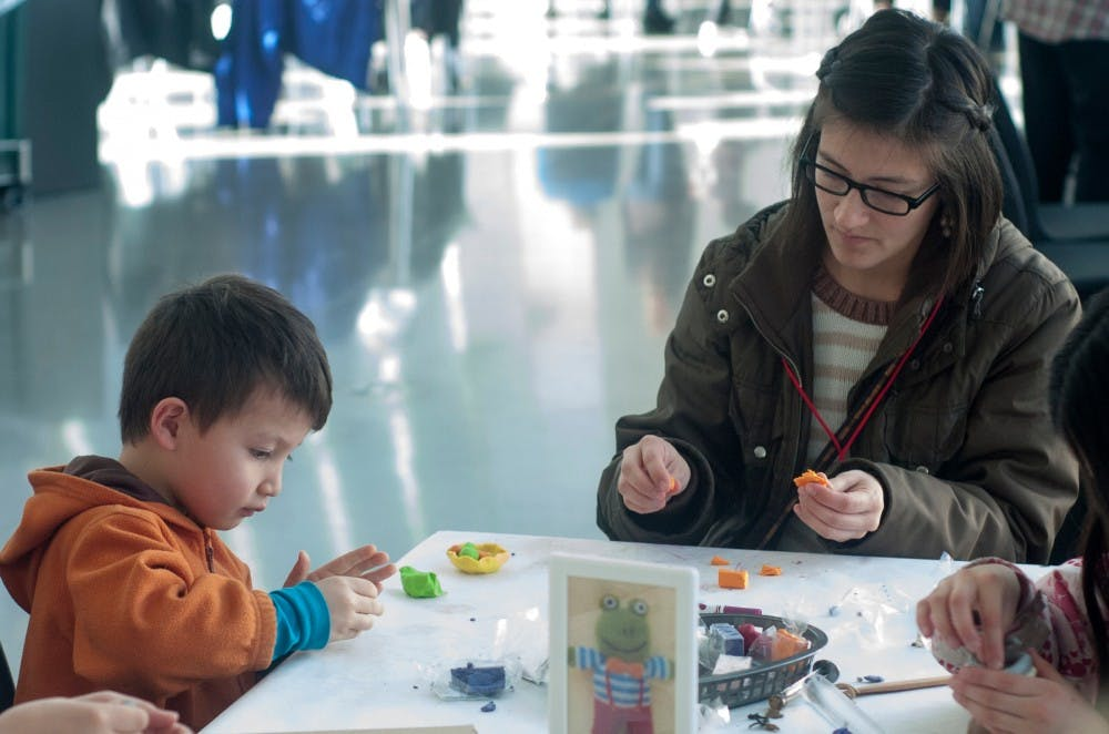 From left to right, Neo Liang, 5, and East Lansing resident Diana Liang make crafts during family day on Feb. 6, 2016 at the Eli and Edythe Broad Art Museum.