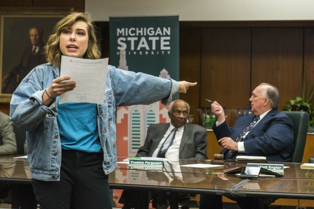 Comparative cultures and politics sophomore Natalie Rogers points towards Interim President John Engler as she disrupts the Board of Trustees meeting and addresses the board on Feb. 16, 2018 at the Hannah Administration Building. (Nic Antaya | The State News)
