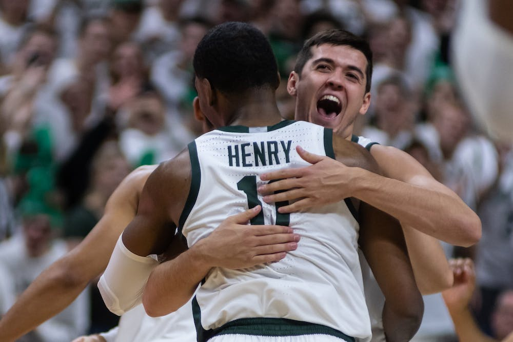 Senior forward Conner George (right) hugs sophomore forward Aaron Henry (11).The Spartans defeated Michigan, 87-69, at the Breslin Student Events Center on January 5, 2020.
