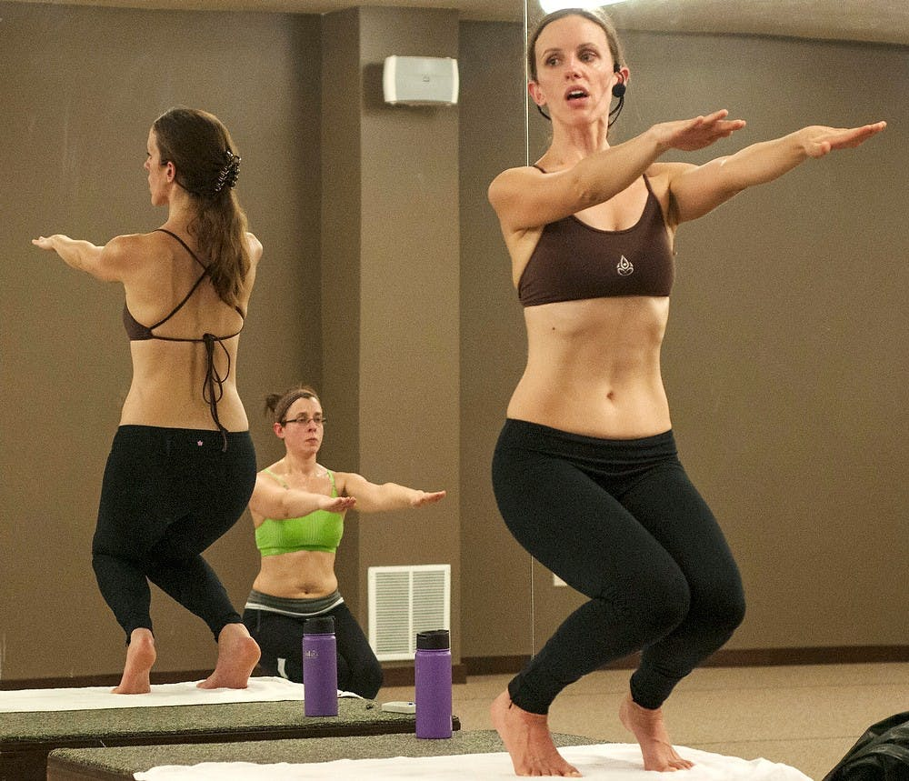 """<p>Bikram Yoga Capital Area owner and <span class=""""caps"""">MSU</span> alumna Ann Chrapkiewicz performs the utkatasana pose during a class Nov. 14, 2013, at her studio, 1355 E. Grand River Ave. Bikram Yoga is done in a 105-degree studio with a variety of poses to get the heart pumping and oxygen flowing.</p>"""