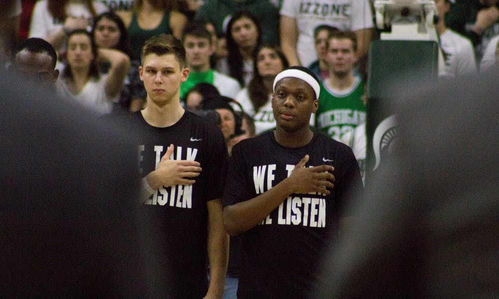 Junior guard Matt McQuaid (20), left, and sophomore guard Cassius Winston (5), right, stand for the national anthem before the game against North Florida on Nov. 10, 2017, at Breslin Center. The Spartans defeated the Ospreys 98-66.