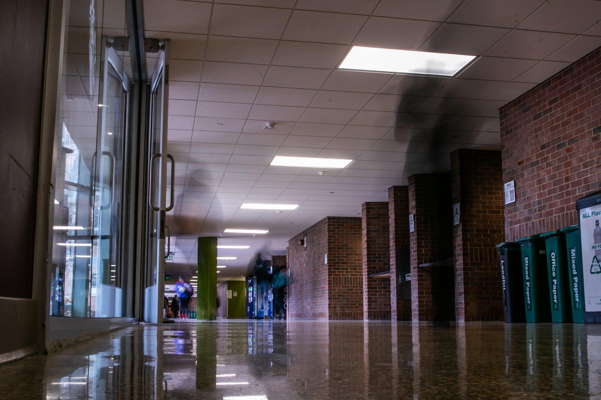People walk through a mostly empty academic building hallway.