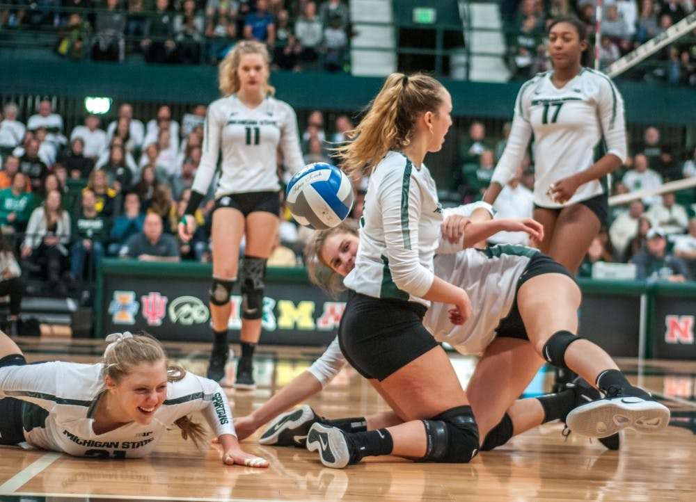 Freshman middle blocker Rebecka Poljan (21) has a laugh after diving to dig a ball during the game against Michigan on Nov. 17, 2018 at Jenison Fieldhouse. The Spartans lost to the Wolverines 3-1.