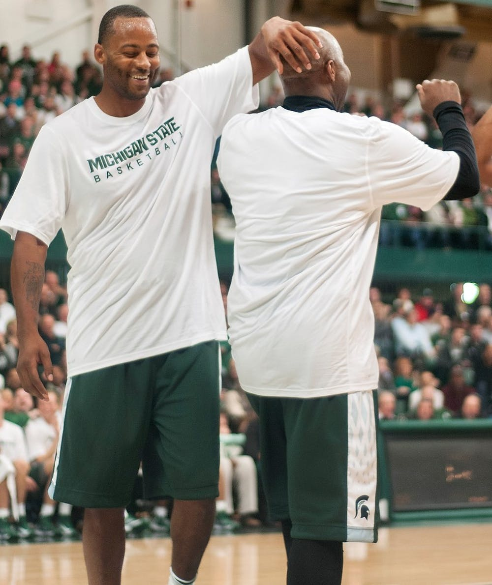 """<p><span class=""""caps"""">MSU</span> Men&#8217;s basketball ex-forward Morris Peterson, left, pats teammate and ex-guard Mateen Cleaves, right, on the head after Cleaves scored during the <span class=""""caps"""">MSU</span> Basketball Alumni Game on Friday, Dec. 14, 2012, in the Jenison Field House. Cleaves and Peterson were part of the winning &#8220;Home&#8221; team, winning the game 125-118. State News File Photo </p>"""