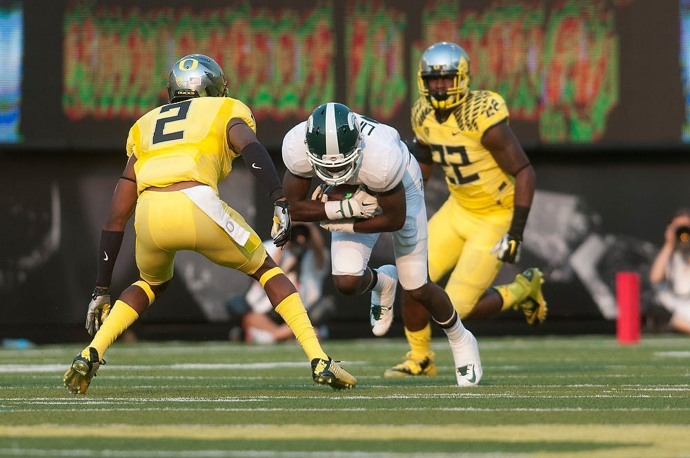<p>Senior wide receiver Tony Lippett braces for Oregon defensive back Tyree Robinson's tackle on Sept. 6, 2014, at Autzen Stadium in Eugene, Ore. The Spartans lost to the Ducks, 46-27. Julia Nagy/The State News</p>
