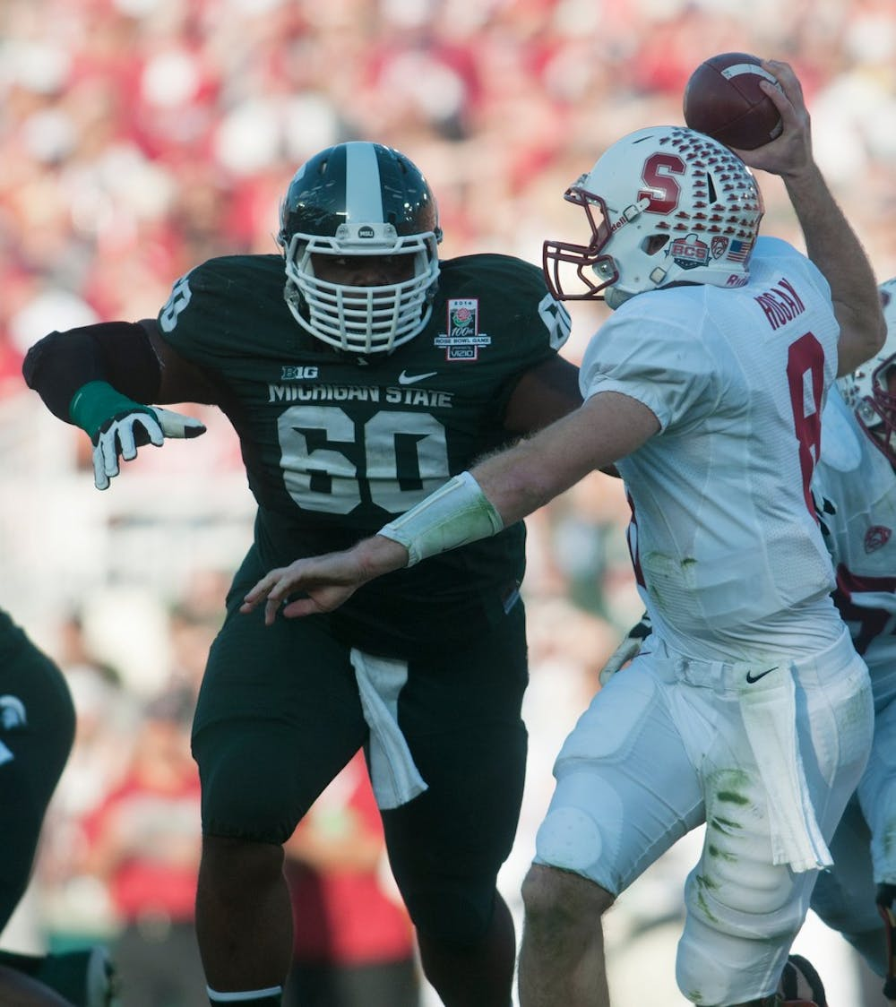 <p>Defensive lineman Micajah Reynolds trys to tackle Stanford quarterback Kevin Hogan during the 100th Rose Bowl on Jan. 1, 2014, in Pasadena, Calif. Julia Nagy/The State News</p>