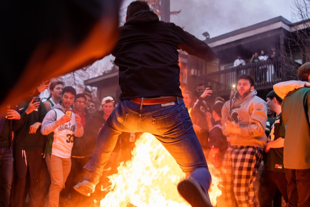 A fan jumps over a burning couch after MSU's victory over Duke in the Elite Eight in Cedar Village Apartments March 31, 2019.