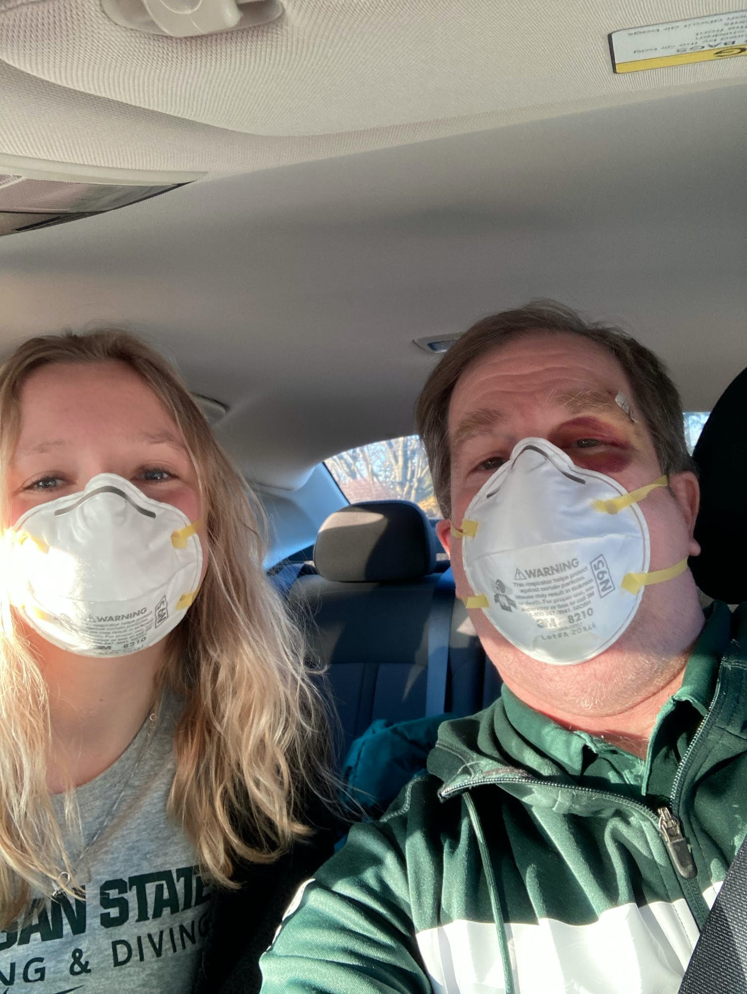 Two people wearing face masks take a selfie while in a car. Both wear Michigan State University clothing.