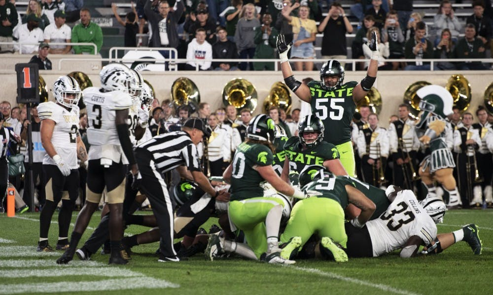 <p>Junior offensive tackle Jordan Reid (55) signifies a touchdown after tackling Western Michigan players. The Spartans crushed the Broncos (51-17) at Spartan Stadium on Sept. 7, 2019. </p>