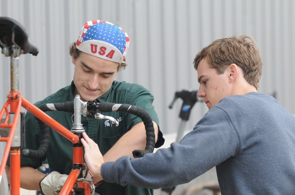 """<p>Environmental studies and sustainability senior Michael Ewing (left) repairs a bike for lifelong education exchange student Guillaume Heral on Sept. 11, 2015 at the MSU Surplus Store. """"I chose a bike for exercising,"""" Heral said. """"I want to ride a bike on campus, I think it's nicer than taking a bus on campus."""" Joshua Abraham/ The State News</p>"""