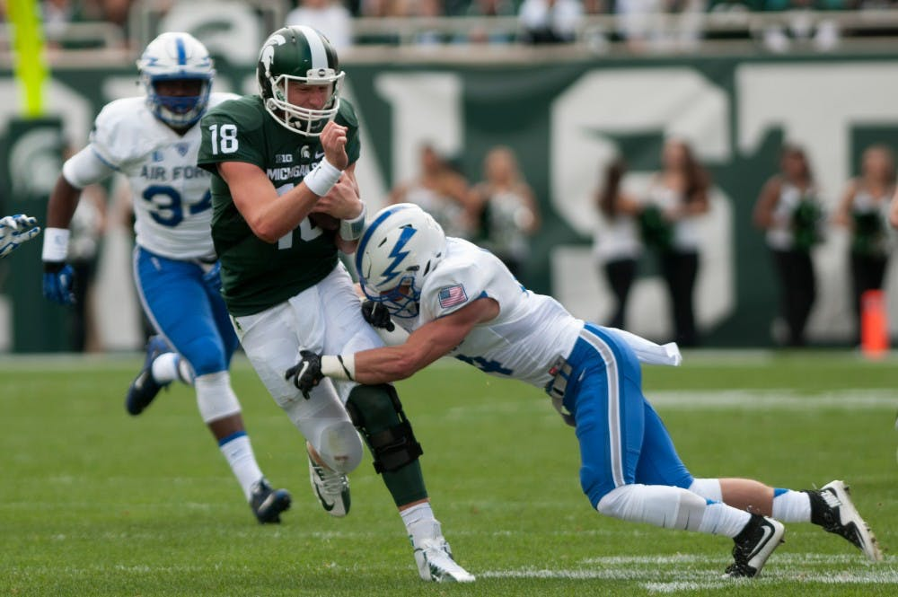 <p>Air Force defensive back Hayes Linn tries to tackle senior quarterback Connor Cook in the first half during the game against Air Force on Sept. 19, 2015 at Spartan Stadium. The Spartans defeated the Falcons, 35-21. Kennedy Thatch/The State News</p>