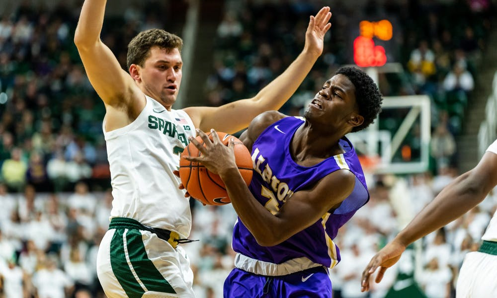 Sophomore guard Foster Loyer (left) defends Albion guard Cortez Garland (right).The Spartans defeated the Britons, 85-50, at the Breslin Student Events Center on October 29, 2019.