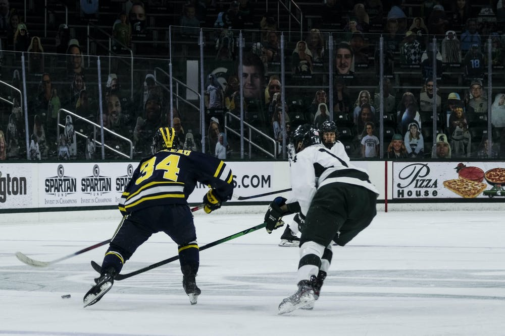 <p>Junior forward Adam Goodsir (14) attempts to steal the puck from Michigan on Jan. 9, 2021, at the Munn Ice Arena. The Spartans defeated the Wolverines, 3-2.</p>